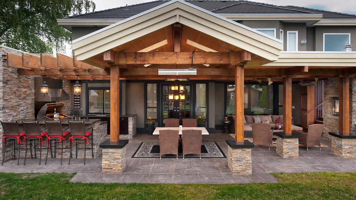 patio with multiple seating areas and outdoor kitchen made with large wood columns with stone bases