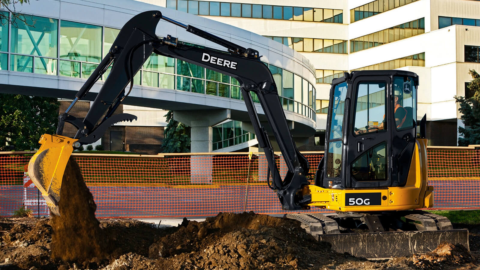 excavator digging dirt next to concrete walkway with large office building in background