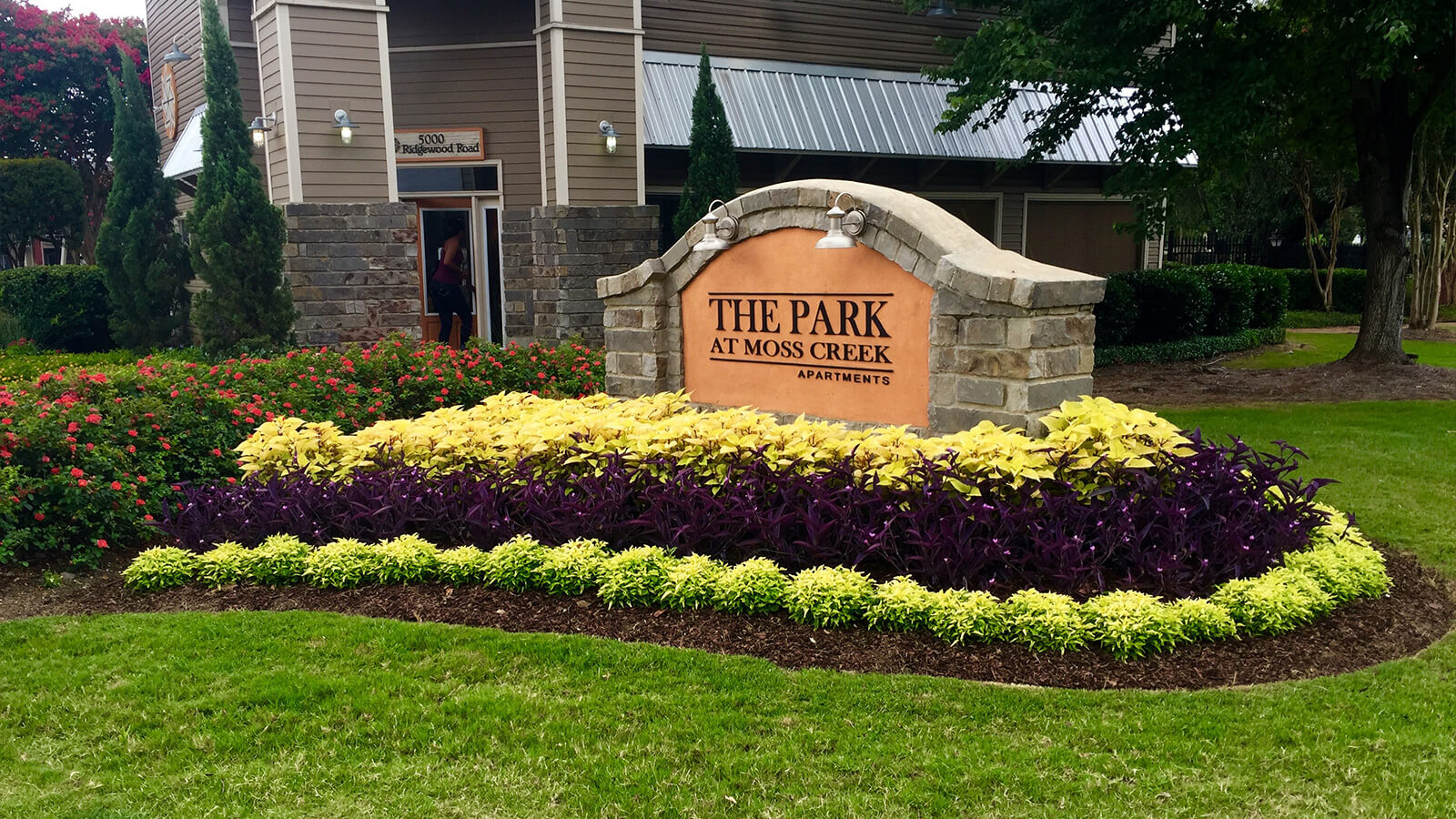sign for The Park apartments with structured flowerbed containing rows of ornamental grass and other colored plants