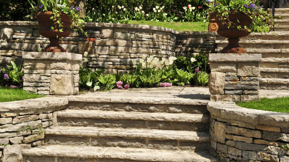 retaining walls made of stone blocks with brick stairway through the middle, flowers edging stairs and planters with flowers on stair way posts