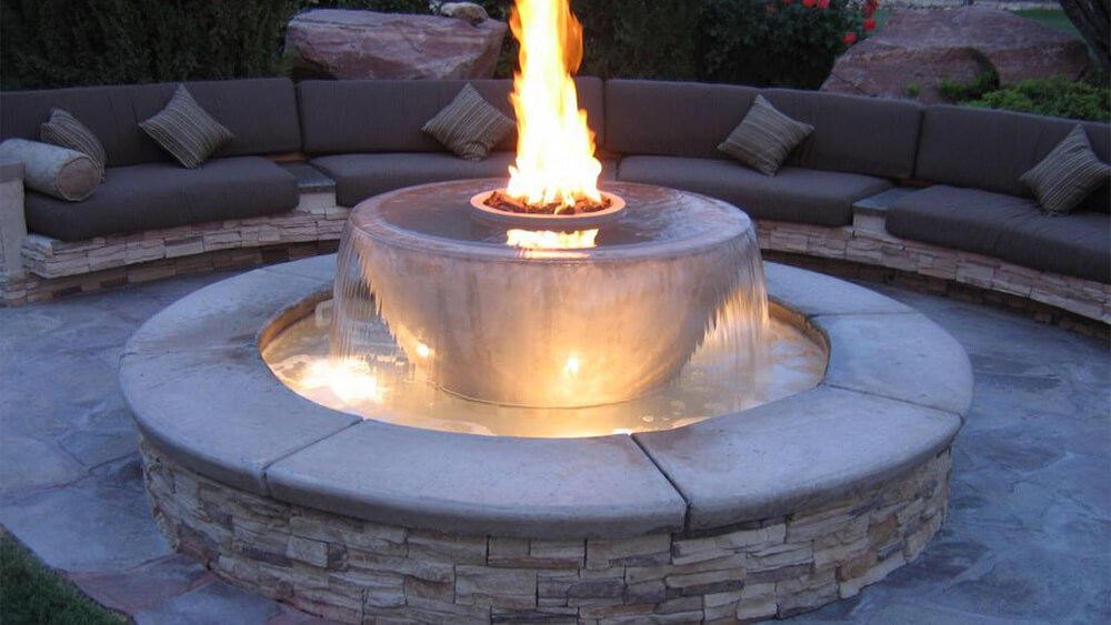 patio with stone bench circle surrounding bowl shaped water fountain with fire at top center