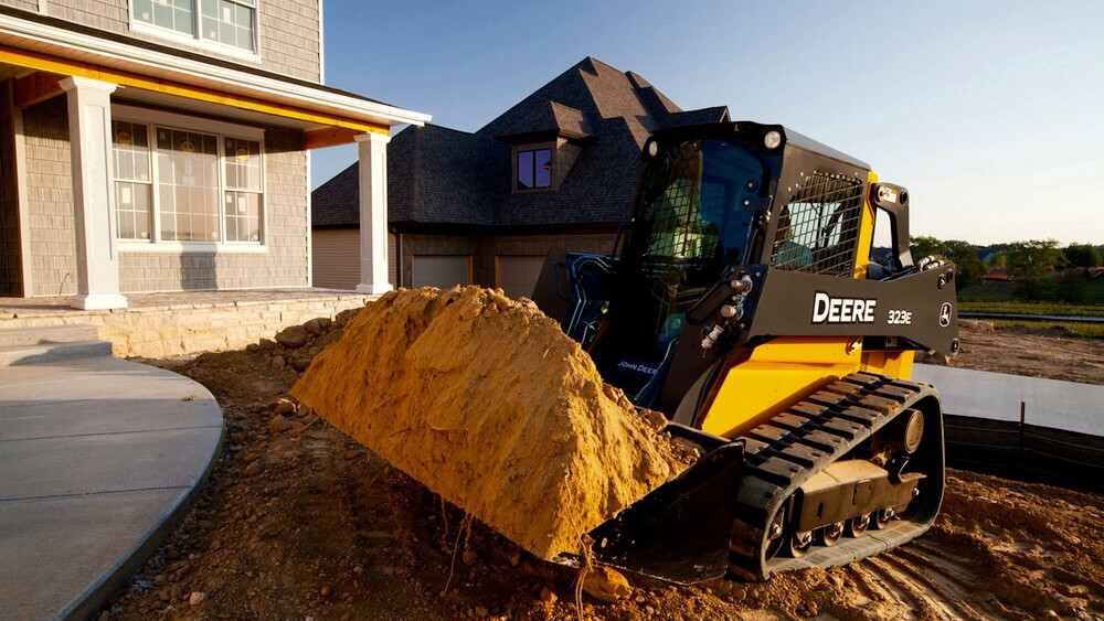 small bulldozer holding scoop of dirt in new construction area