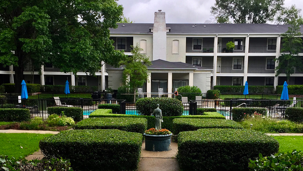 courtyard with pool surrounded by well trimmed hedges and landscaping