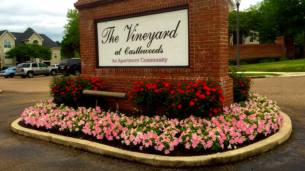 sign for The Vineyard apartments surrounded by flowerbed